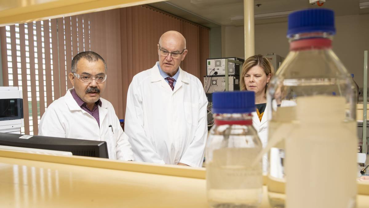 Tursun Kerim shows Professor John Skerritt and Dr Lisa Kerr his current work with the COVID-19 vaccine. Picture: Keegan Carroll